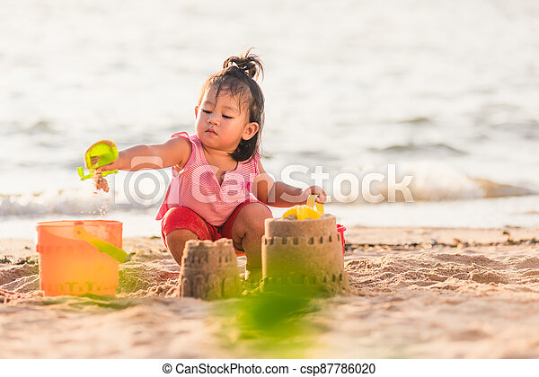 little girl playing sand with toy sand tools - csp87786020