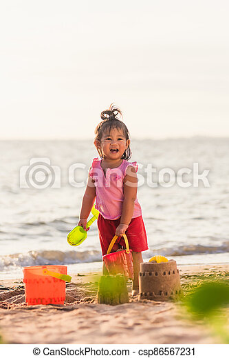 little girl playing sand with toy sand tools - csp86567231