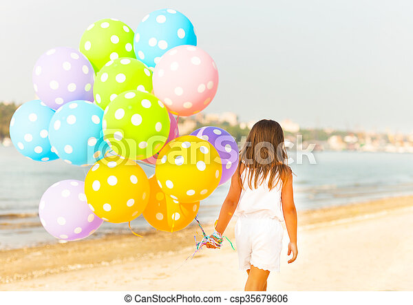 Little girl playing with balloons at the beach - csp35679606