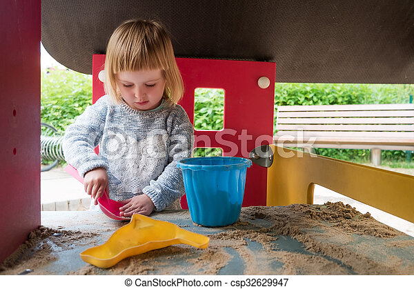 little girl playing with sand - csp32629947