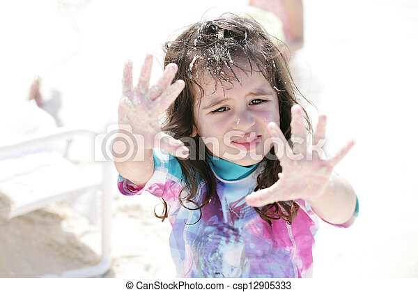 Little girl playing with sand. - csp12905333