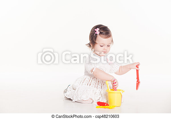 little girl plays with toys on a white background - csp48210603