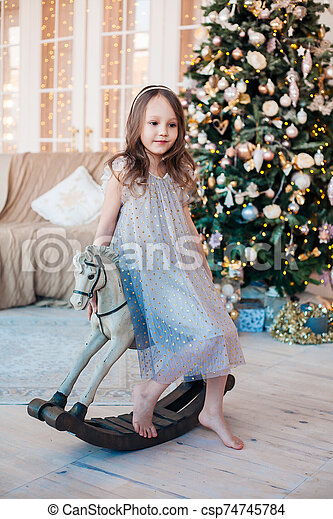 little girl posing on antique rocking horse against Christmas tree indoors. - csp74745784