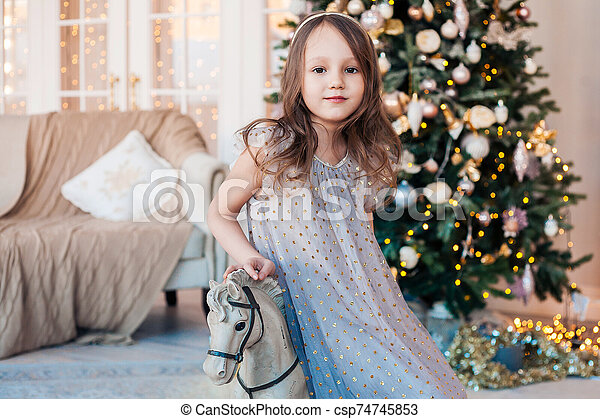 little girl posing on antique rocking horse against cozy interior with Christmas tree. - csp74745853