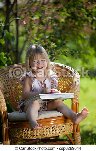 Little girl reading book sitting in wicker chair outdoor in summer day - csp8269044