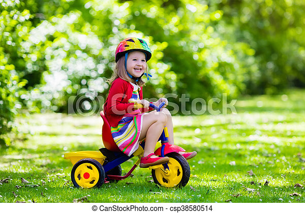 2264465ecdc Little girl riding a tricycle. Cute girl wearing safety helmet ...