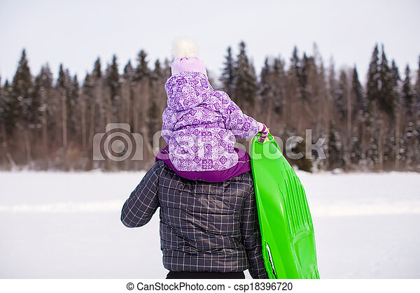 Little girl riding on young father outdoors in cold winter day - csp18396720