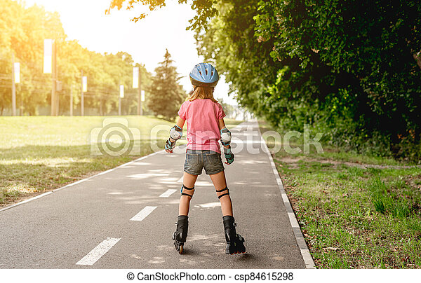 Little girl roller skating in park - csp84615298