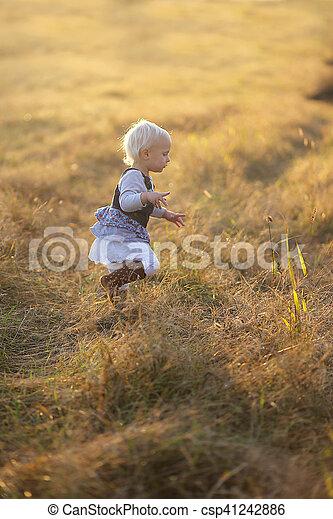 Little Girl Running Through Golden Field at Sunset - csp41242886