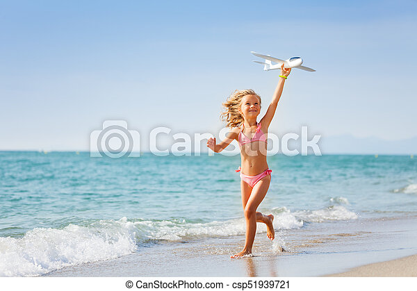 Little girl running with toy plane on the beach - csp51939721
