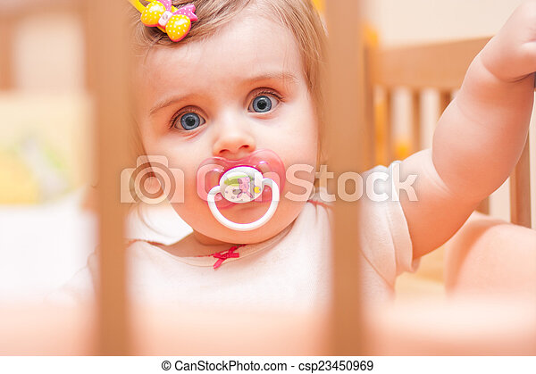 little girl sitting in a crib with - csp23450969