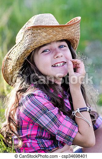 71dc1c9cdae83 Little girl sitting in a field wearing a cowboy hat. Cute child ...