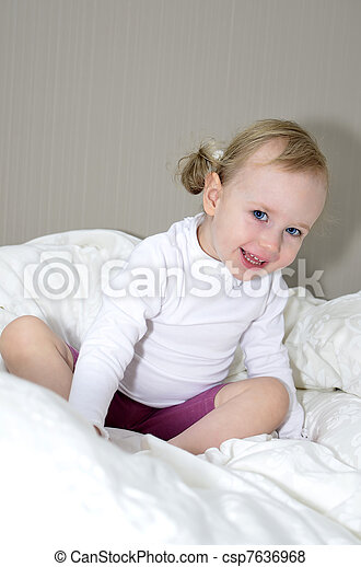 Little girl sitting on a bed and smiling.