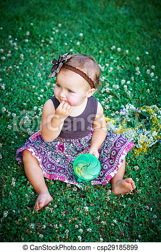 little girl sitting on the grass - csp29185899