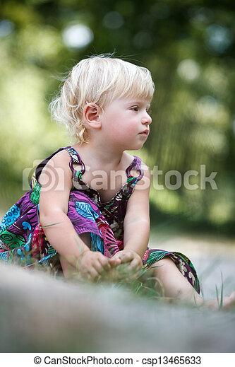 little girl sitting on the ground - csp13465633