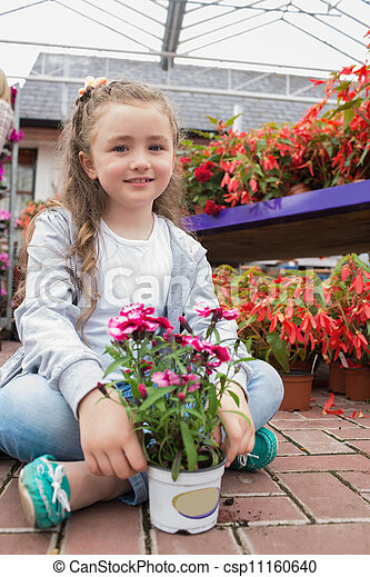 Little girl sitting on the path with a flower - csp11160640