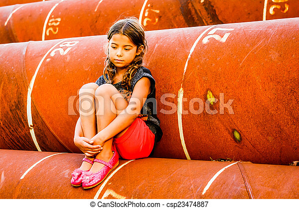 Little girl sitting on the pipes - csp23474887