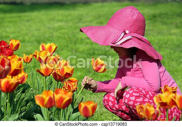little girl smell tulip flower spring scene - csp13719083