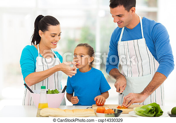 little girl tasting tomato while parents cooking - csp14330329