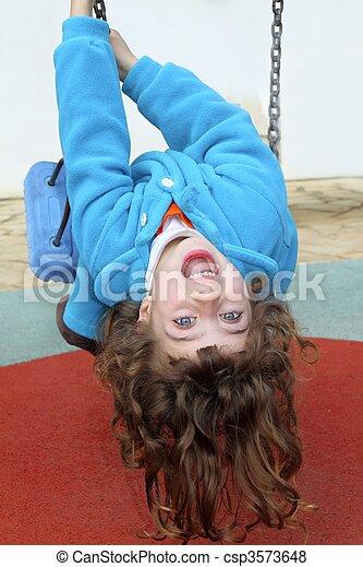 little girl upside down on park playground swing - csp3573648