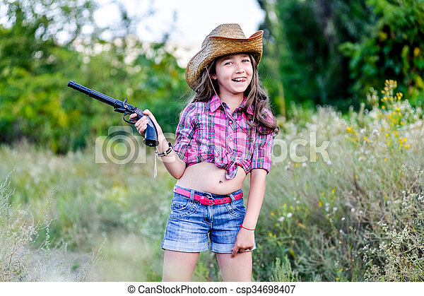 26cc27369aa7f Little girl with a toy gun in his hand standing in a field. Cute ...