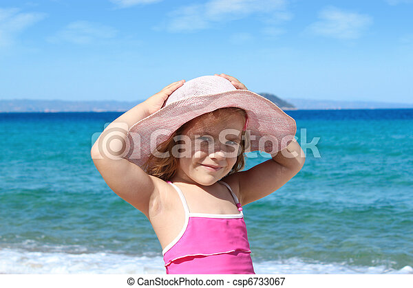 little girl with straw hat on beach - csp6733067