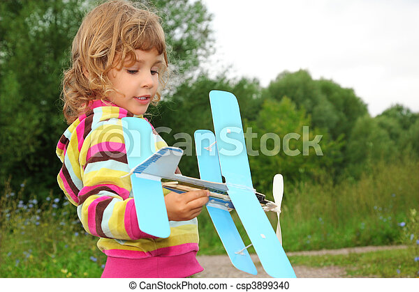 little girl with toy airplane in hands outdoor - csp3899340