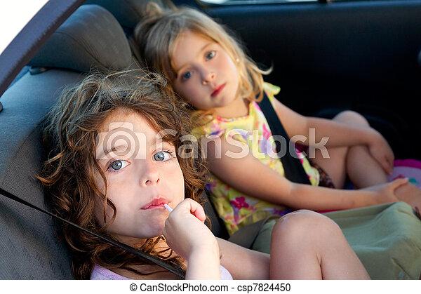 little girls inside car eating candy stick - csp7824450