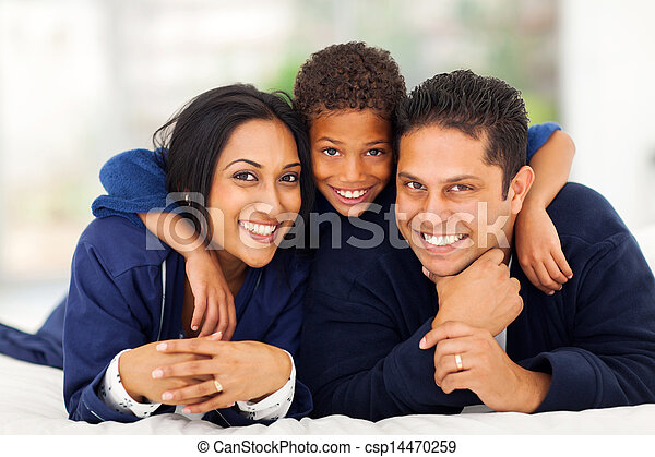 little indian boy hugging his parents on bed - csp14470259