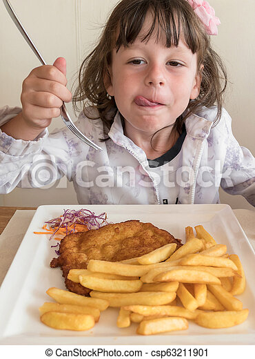Little Italian girl eating breaded meat and french fries - csp63211901