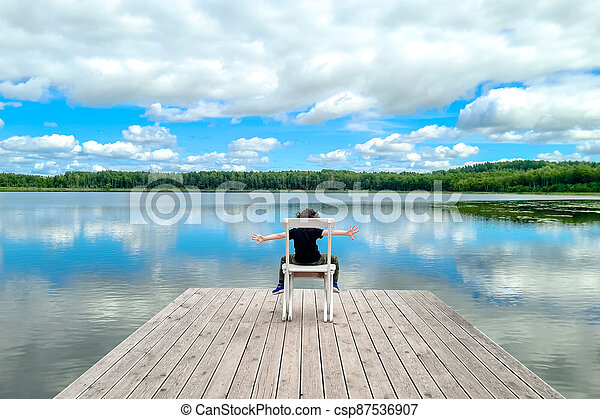 Little man sitting on white empty deck chair at the lake dock. - csp87536907