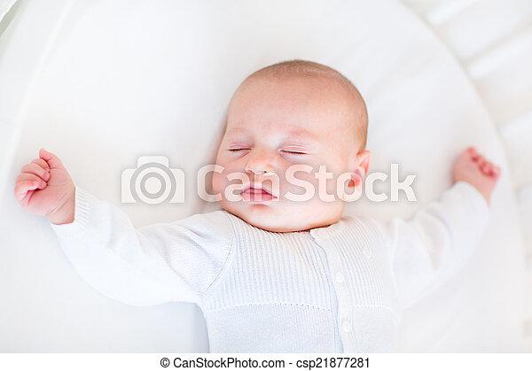 Little newborn baby boy sleeping in a white round crib  - csp21877281