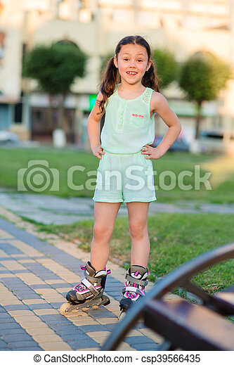 Little pretty girl on roller skates at a park - csp39566435