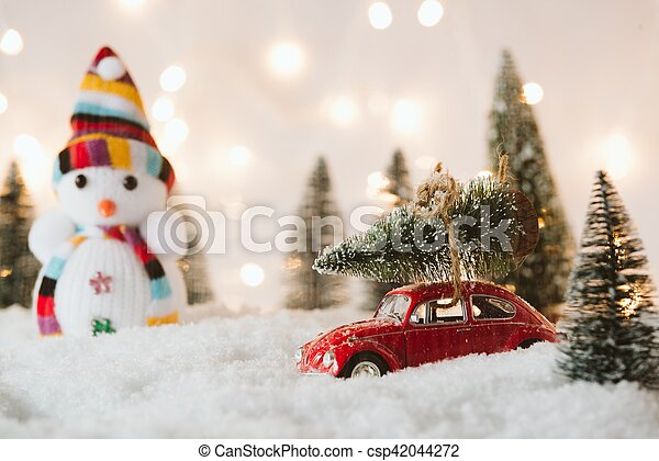 Little red car toy carrying Christmas tree - csp42044272