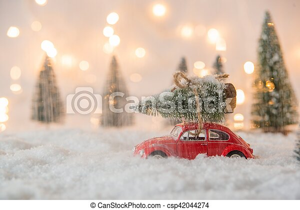 Little red car toy carrying Christmas tree - csp42044274