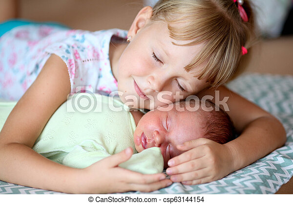 948245912249a Little sister hugging her newborn brother. Toddler kid meeting new sibling.  Cute girl and new born baby boy relax in a white bedroom. Family with ...