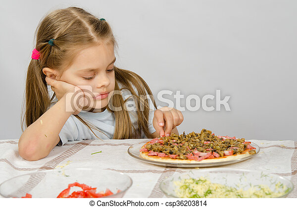 Little six year old girl sitting at the table and picks unfinished pizza - csp36203814