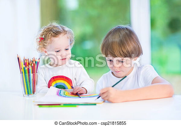 Little toddler girl watching her brother drawing with colorful p - csp21815855