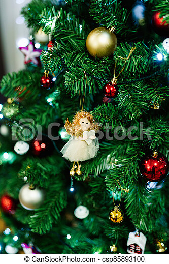 Little toy angel on the branches of a Christmas tree. - csp85893100