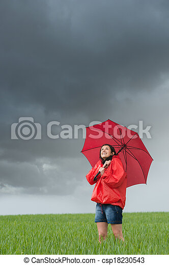 lively girl daydreaming on rainy day on field with umbrella