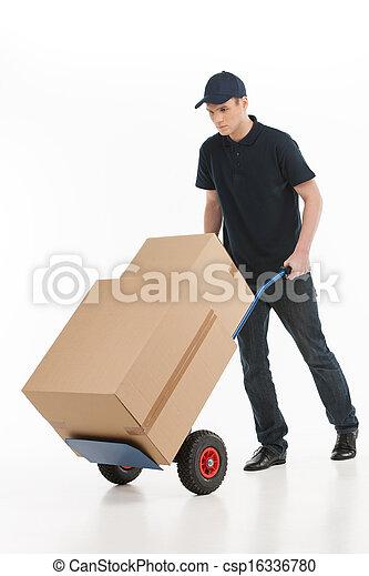Casa de mudanzas. A lo largo del joven repartidor con un camión de mano transportando las cajas de cartón - csp16336780