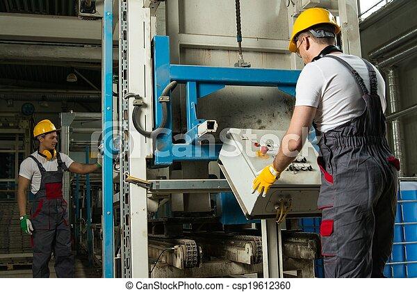 Operadora usando sombrero de seguridad detrás del panel de control en una fábrica - csp19612360