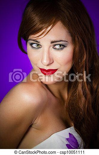 Una foto de una hermosa mujer con el pelo rojo usando hermosas joyas sobre un fondo púrpura - csp10051111