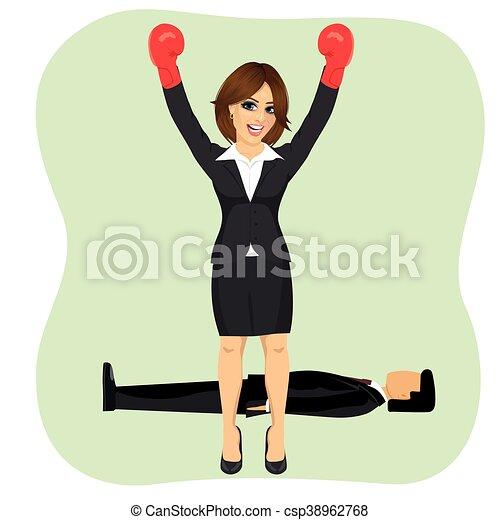 Mujer de negocios de éxito animando con brazos levantados usando guantes de boxeo delante del hombre tirado en el suelo - csp38962768