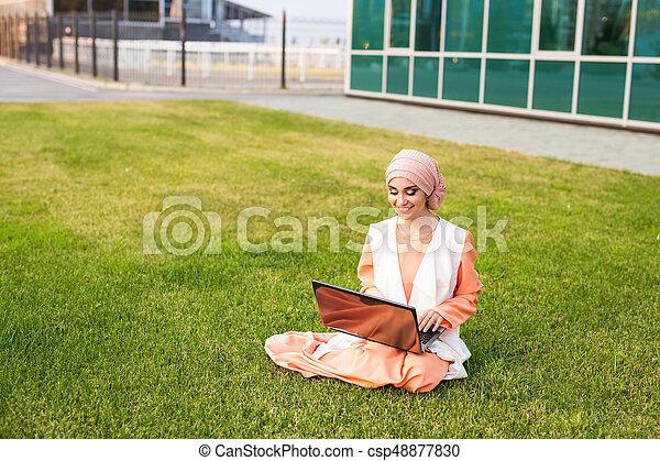 Mujer árabe exitosa y portátil. Una mujer de negocios árabe usando un hijab trabajando en un portátil en el parque. - csp48877830