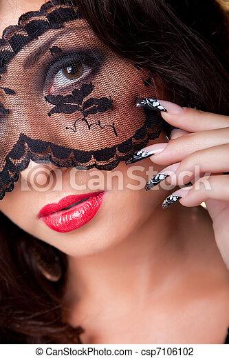 Un retrato de una joven morena atractiva con largos anillos oscuros. Una bella manicura de arte usando máscara de encaje en sus ojos - csp7106102