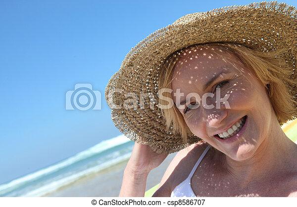 Mujer en la playa con sombrero de paja - csp8586707