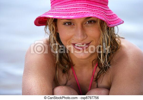 Mujer rubia usando un sombrero rosa en la playa - csp8797756