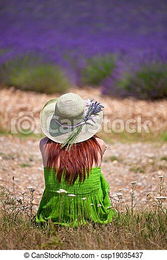 Una dama romántica vestida de verde y sombrero, sentada frente al campo de lavanda violeta. Cerca, retrovisor. El sombrero está decorado con ramitas de lavanda. - csp19035437