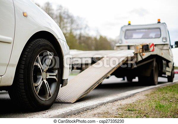 Loading broken car on a tow truck on a roadside - csp27335230
